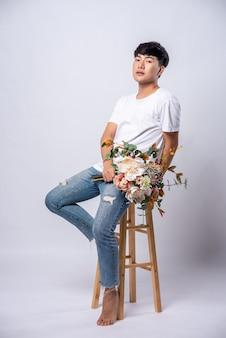 Un giovane con una maglietta bianca si siede su un seggiolone e tiene dei fiori.