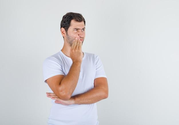 Giovane uomo in maglietta bianca in piedi con la mano vicino alla bocca e guardando pensieroso
