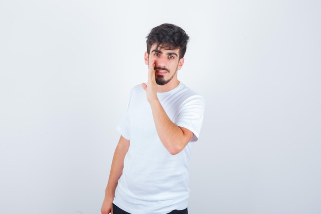 Young man in white t-shirt telling secret behind hand and looking confident