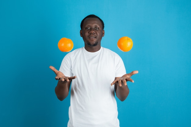 Young man in white t-shirt throwing up two sweet orange fruits against blue wall