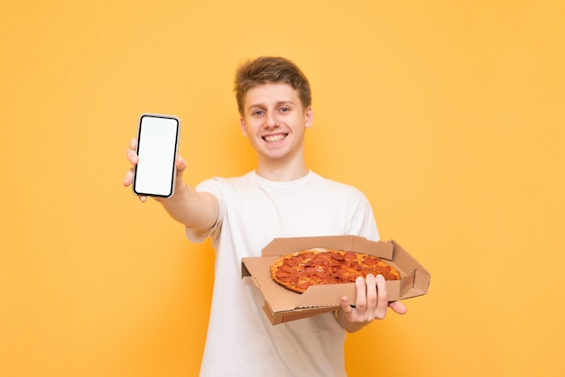 Young man in a white t-shirt with a box of pizza in his hands, standing on a yellow, shows a smartphone with a white screen in the camera and smiles
