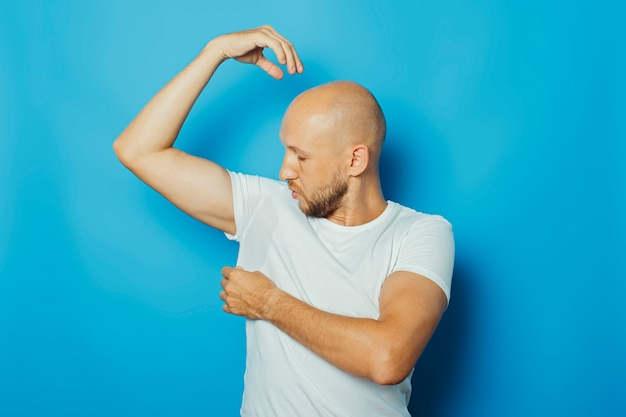 Young man in a white t-shirt with wet armpits from sweat on a blue background