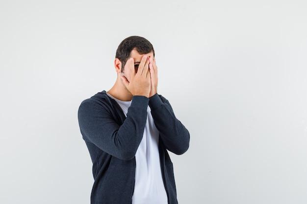 Giovane in maglietta bianca e felpa con cappuccio nera con zip frontale che copre il viso con le mani e sembra dispiaciuto, vista frontale.