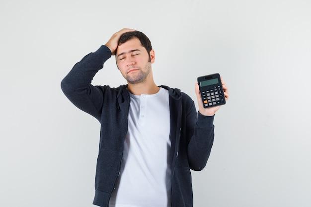 Giovane uomo in maglietta bianca e felpa con cappuccio nera con zip frontale che tiene calcolatrice e mette la mano sulla testa e sembra ottimista, vista frontale.