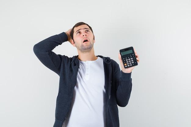 Giovane uomo in maglietta bianca e felpa con cappuccio nera con zip sul davanti che tiene calcolatrice e mettendo la mano sulla testa e guardando pensieroso, vista frontale.