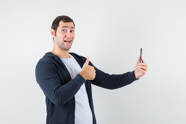 Young man in white t-shirt and zip-front black hoodie holding smartphone, showing thumb up and looking happy , front view.