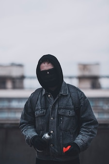 Молодой человек, который прячет лицо, готовится сделать граффити.