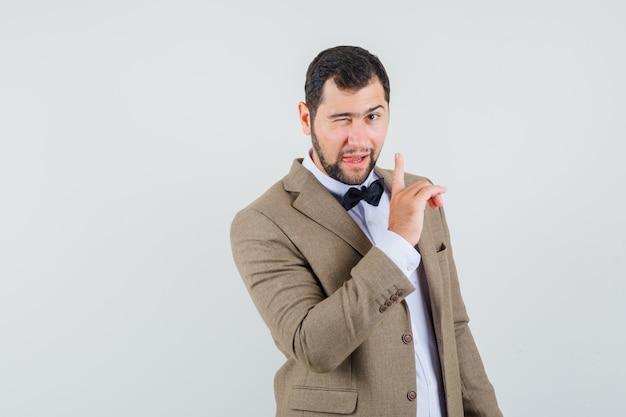 目をまばたきし、スーツ、正面図で沈黙のサインを示している若い男。