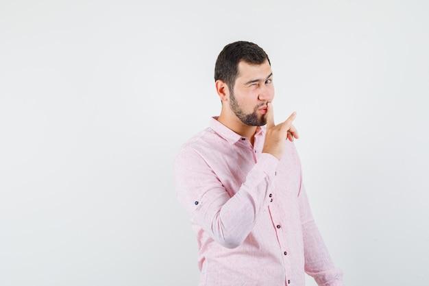 目をまばたき、ピンクのシャツで沈黙のジェスチャーを示し、エレガントに見える若い男