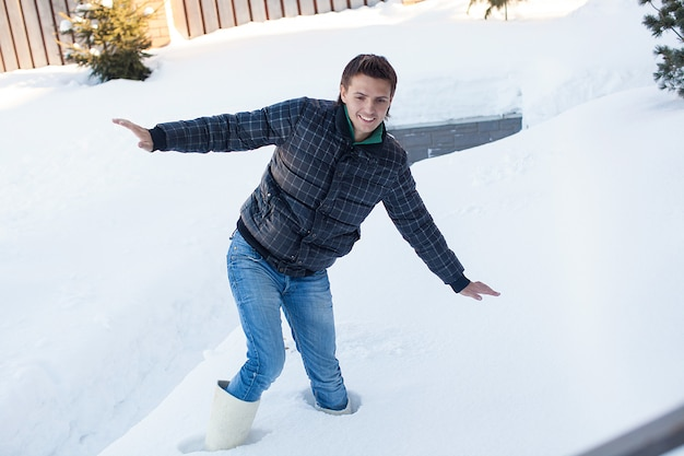 Young man in winter boots fell into a deep white snow