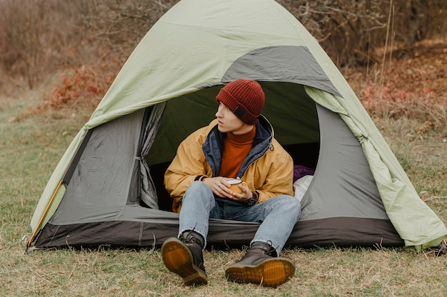 Young man on winter trip with tent