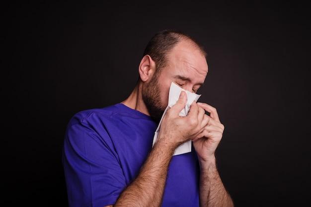 若い男が暗い背景にペーパータオルで鼻を拭く-covid-19