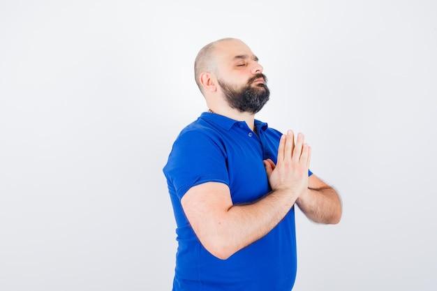 青いシャツを着て落ち着いて見える若い男。正面図。