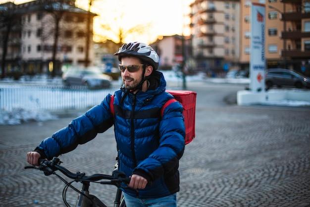 음식 배달 배낭과 자전거 보호 헬멧 젊은 남자. 집에서 일, 자전거 타기, 피자 배달