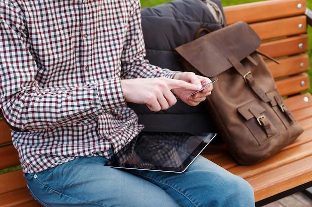 バックパックを持つ若者は、クレジットカードとタブレットコンピューターを保持している公園に座っています。