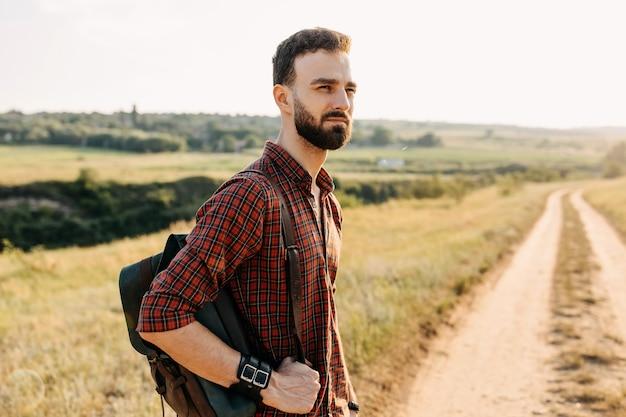 Молодой человек с рюкзаком, стоя на пути в поле, на открытом воздухе.