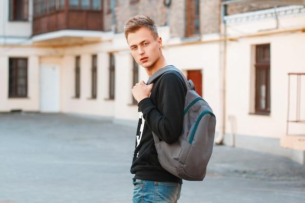 街を旅するバックパックを持つ若い男