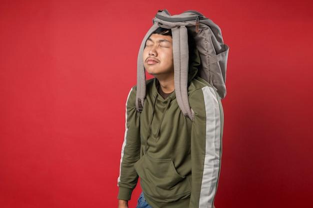 Молодой человек с сумкой на голове устал после дня в школе, изолированные на красном фоне