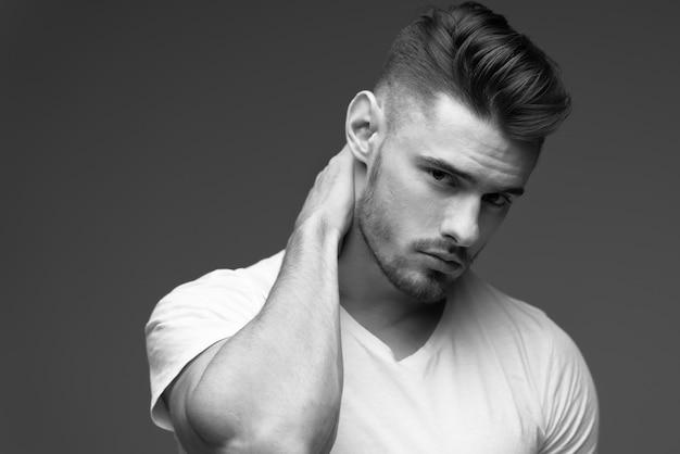 ひげを持つ若い男。 tシャツを着た男性。灰色の背景に男性の肖像画。スタイリッシュな男。黒と白の写真。スポーツ男。男性フィットネスモデル。スタジオポートレート