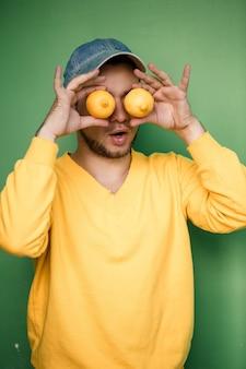 Молодой человек с бородой в кепке на голове с лимонами на глазах на зеленом фоне. портрет парня в желтом свитере