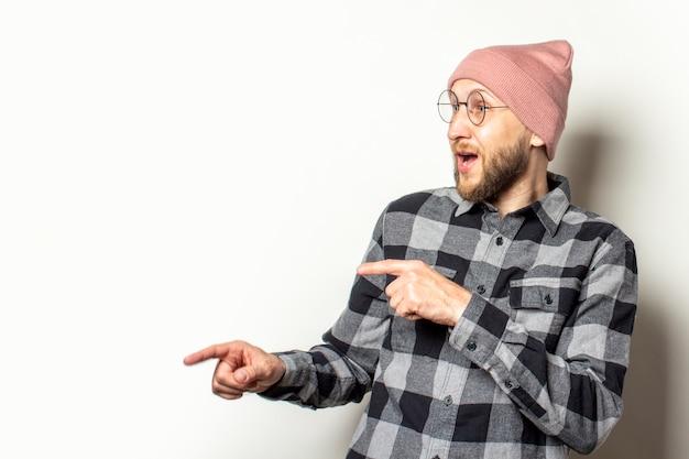 帽子のひげ、格子縞のシャツとメガネを持つ若い男は、孤立した白の驚いた顔のある側に指を向けます。ジェスチャーはそれを見て
