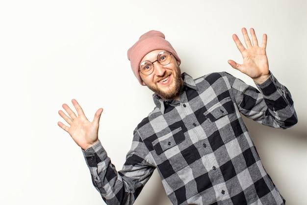 帽子のひげを持つ若い男、格子縞のシャツは分離白の画像の端の後ろからのぞきます。ジェスチャーサプライズショック