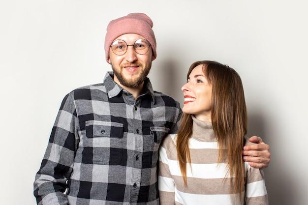 Молодой человек с бородой в шляпе и клетчатой рубашке обнимает девушку в свитере на изолированном свете