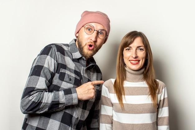 Молодой человек с бородой в шляпе и клетчатой рубашке с удивленным лицом обнимает девушку в свитере и указывает на нее пальцем на свет