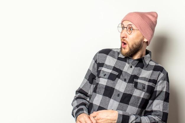 ひげの帽子、格子縞のシャツとメガネを持つ若い男は分離白に驚いた顔が付いている側に見えます。