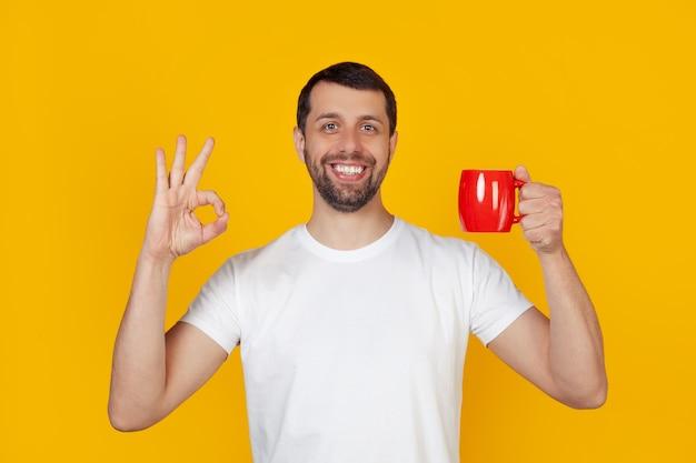 Молодой человек с бородой в белой футболке улыбается, держит красную чашку кофе и показывает жест, все в порядке, мужчина со счастливым лицом.