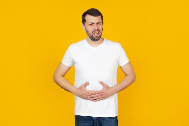 消化不良のために胃に手を当てた白いtシャツのひげを生やした若い男は、気分が悪くなりました。