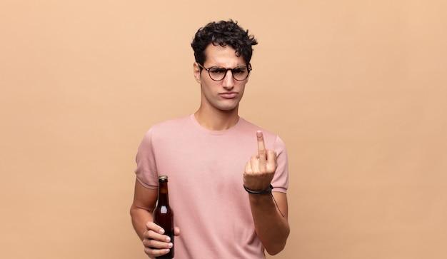 怒り、イライラ、反抗的、攻撃的なビールを感じ、中指をひっくり返し、反撃する若い男