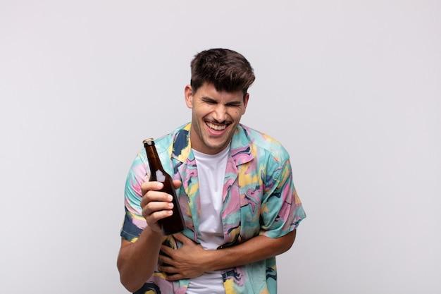 재미있는 농담에 큰 소리로 웃고, 행복하고 쾌활한 느낌, 재미를 느끼는 맥주와 함께 젊은 남자