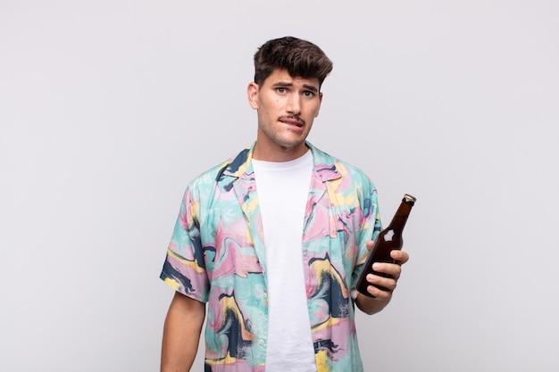 Молодой человек с пивом выглядит озадаченным и сбитым с толку, нервно закусив губу, не зная ответа на проблему