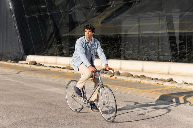 屋外で自転車を持っている若い男