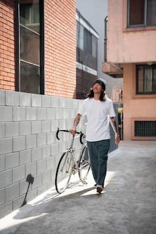 Молодой человек с велосипедом в городе