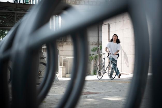 Молодой человек с велосипедом на открытом воздухе