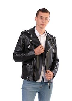 Молодой человек в черной кожаной куртке на белой стене