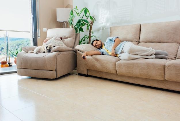 Молодой человек со скучающим, усталым взглядом держит пульт от телевизора и отдыхает на диване