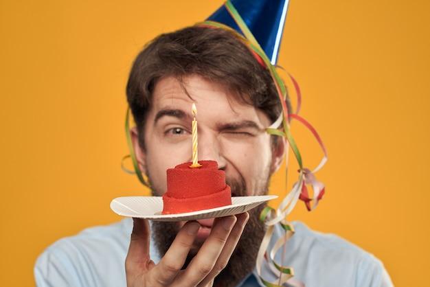スライスとお祝いケーキの若い男がキャップで誕生日を祝う