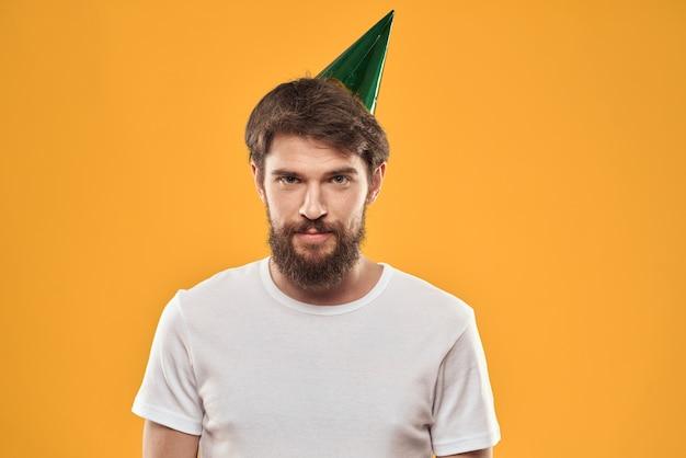 Молодой человек с праздничным тортом с кусочками отмечает день рождения в кепке, изоляции и карантине