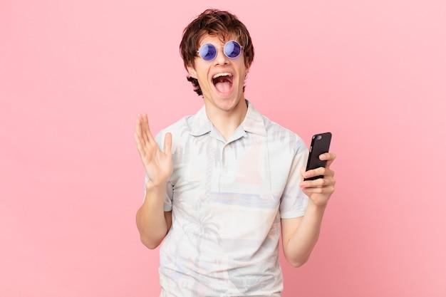 Молодой человек с мобильным телефоном чувствует себя счастливым и удивлен чему-то невероятному