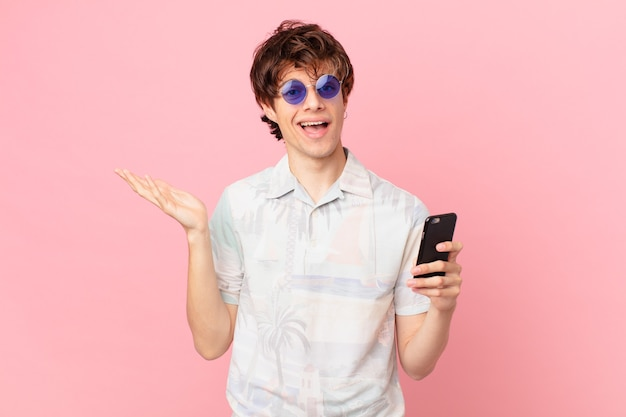 행복한 느낌의 휴대 전화를 가진 젊은 남자가 솔루션이나 아이디어를 깨닫고 놀랐습니다.