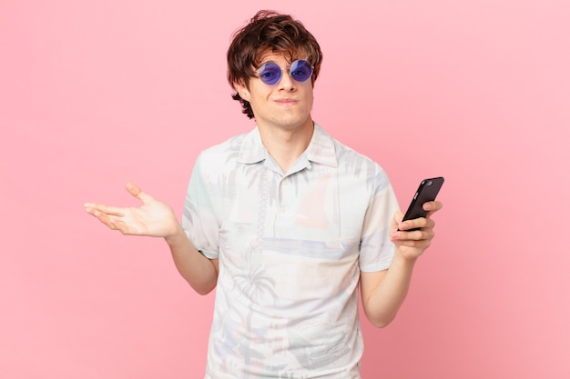 의아해하고 혼란스럽고 의심스러운 휴대 전화를 가진 젊은 남자