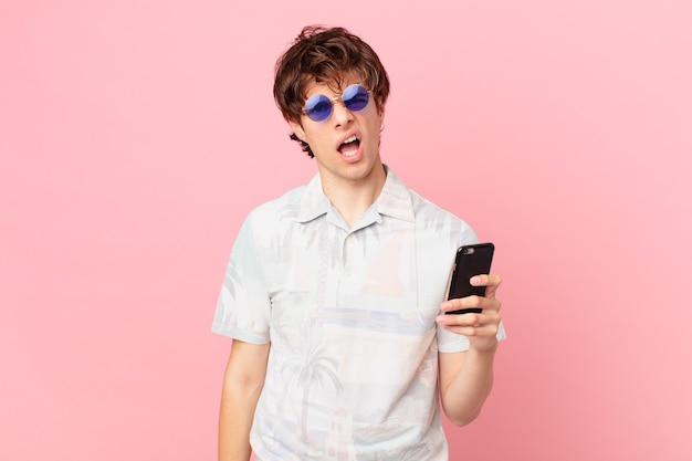 의아해하고 혼란스러워하는 휴대 전화를 가진 젊은 남자