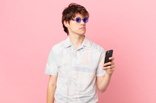 Молодой человек с мобильным телефоном грустит, расстроен или зол и смотрит в сторону