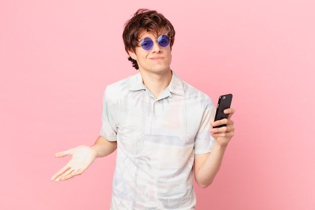 혼란스럽고 불확실한 느낌을 으쓱하는 휴대 전화를 가진 젊은 남자
