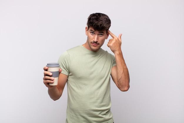 混乱して困惑していると感じているコーヒーを飲んでいる若い男