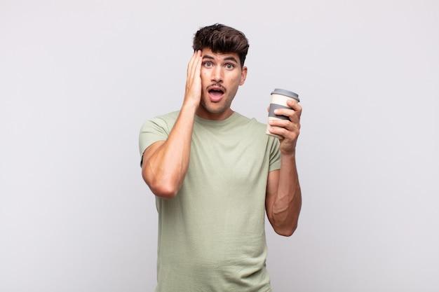 Молодой человек с кофе чувствует себя счастливым, взволнованным и удивленным, глядя в сторону обеими руками на лице