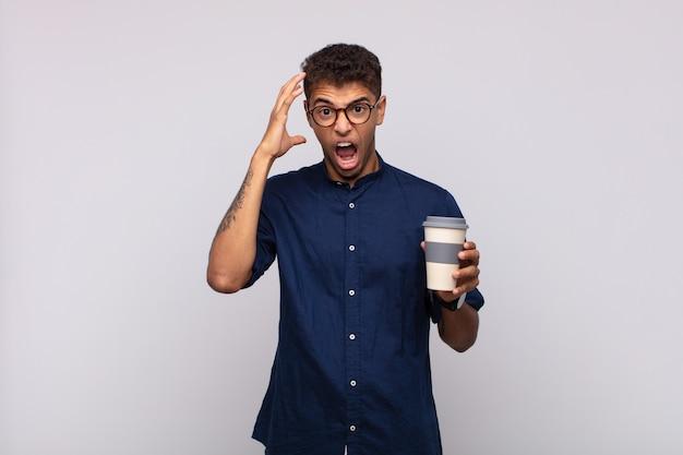 空中で手を上げて叫んで、激怒、欲求不満、ストレス、動揺を感じてコーヒーを飲みながら若い男